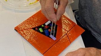 Hand working on an orange piece of glass