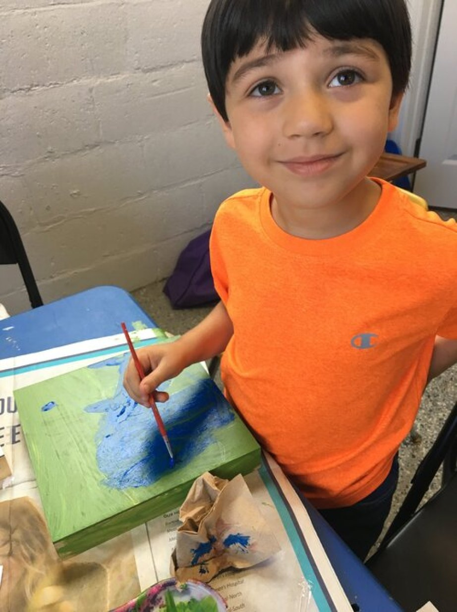 A little boy in an orange t-shirt smiling at the camera and painting