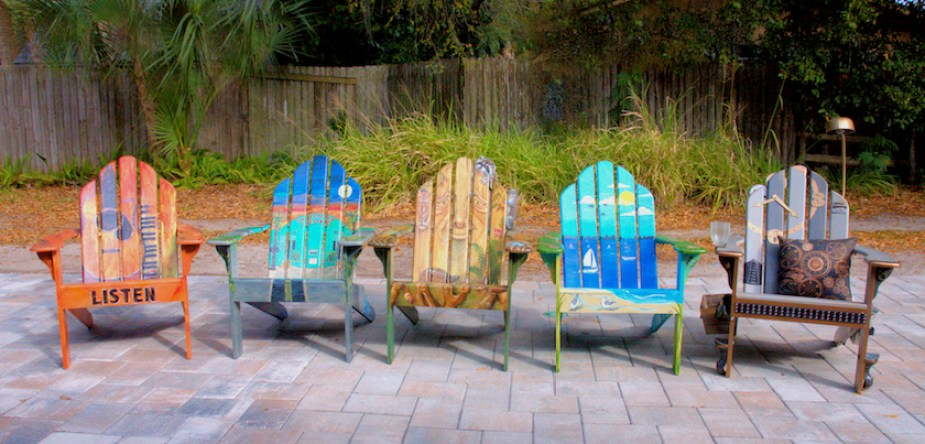 A photo of artistically painted wooden Adirondack chairs