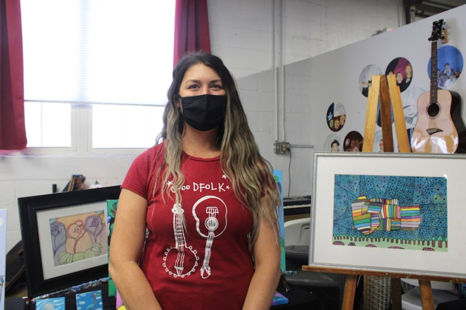 A woman in an art studio wearing a red t-shirt and a black face mask.