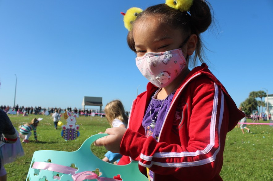 A girl in pigtails wearing a face mask and holding an Easter basket