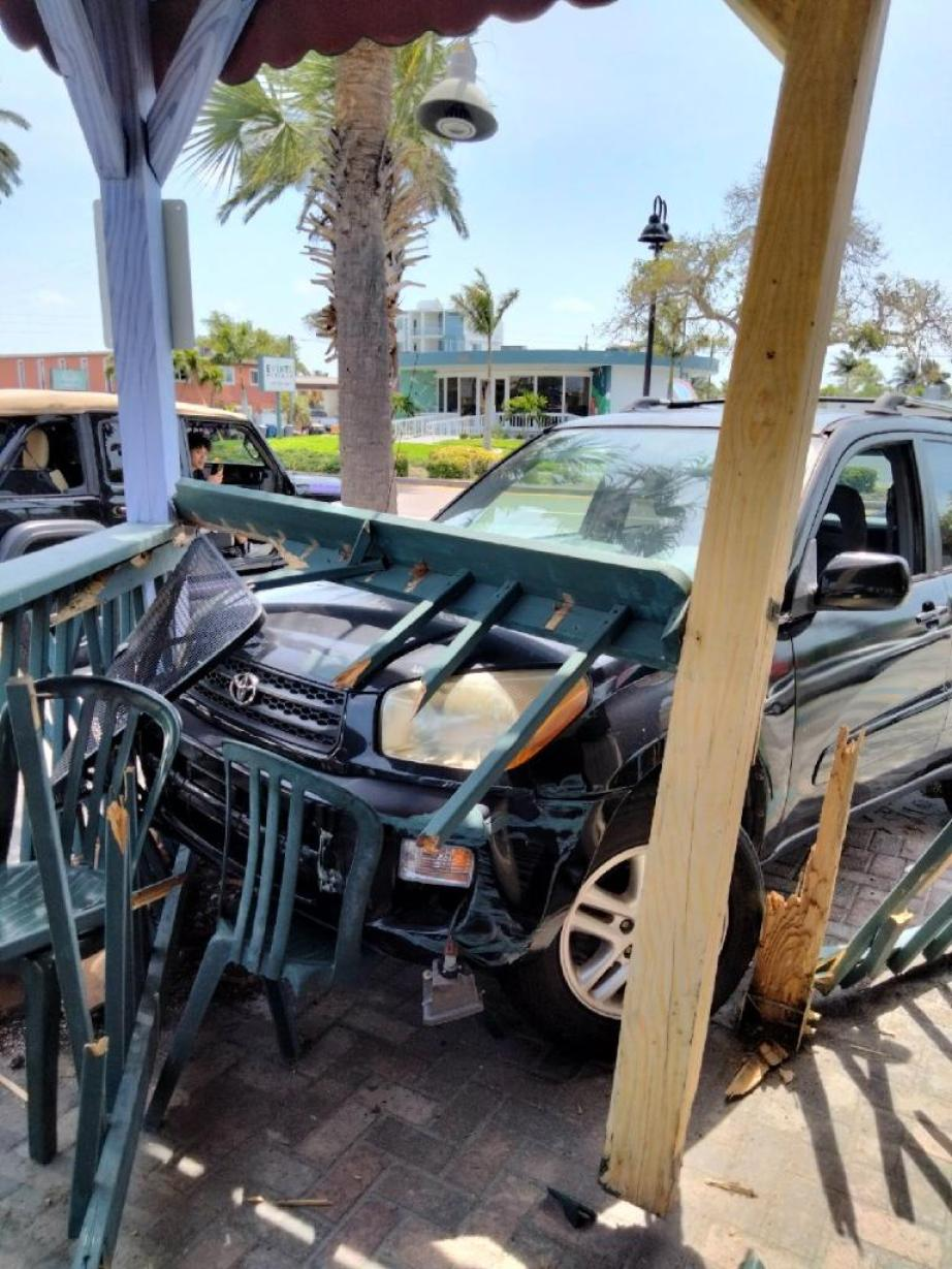 Photo of an outdoor restaurant patio with damage from a car crash.