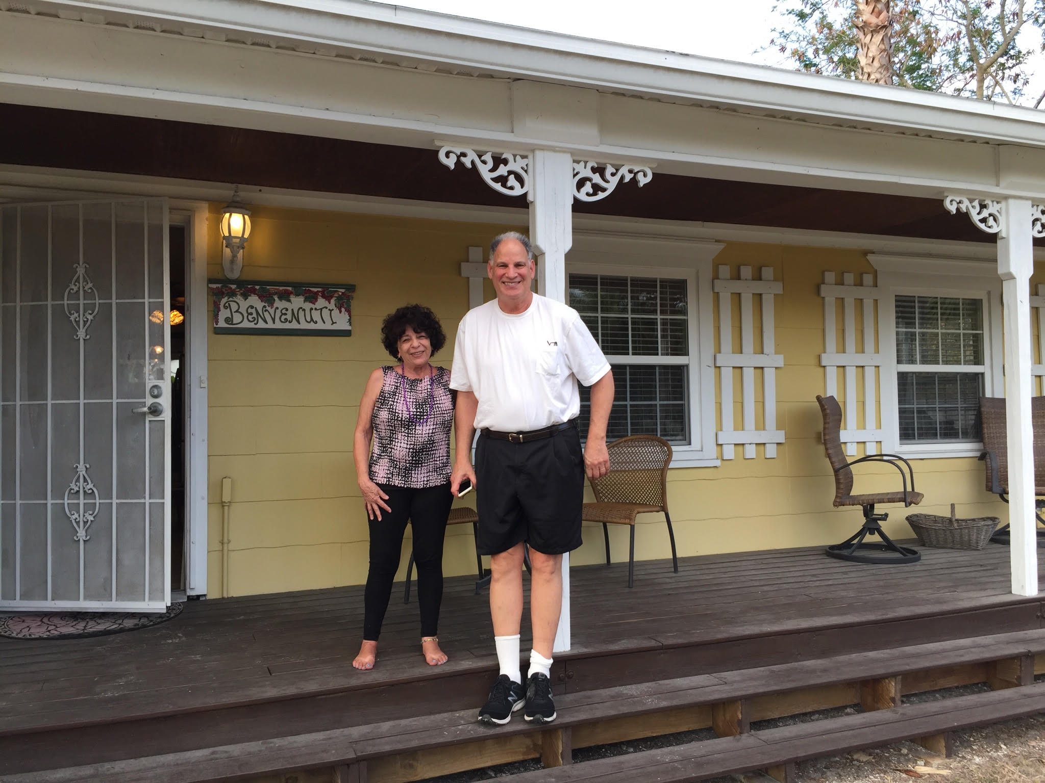 A tall man and short woman standing on a front porch and smiling for the camera.