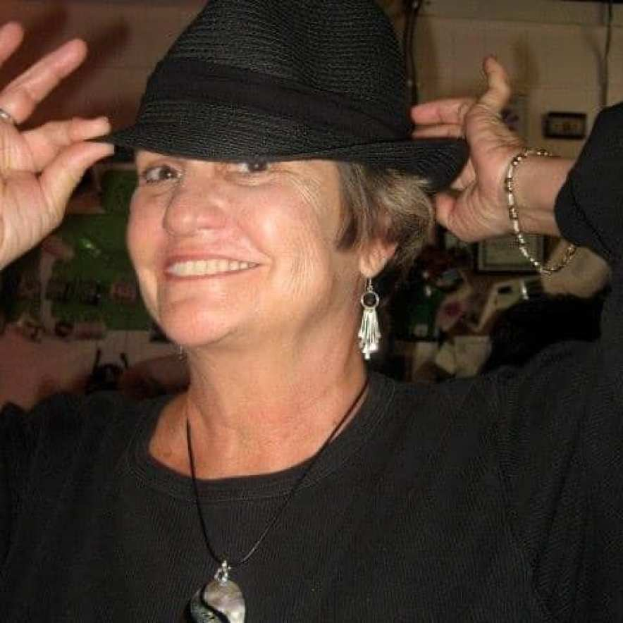 A woman smiling at the camera putting on a black fedora hat.