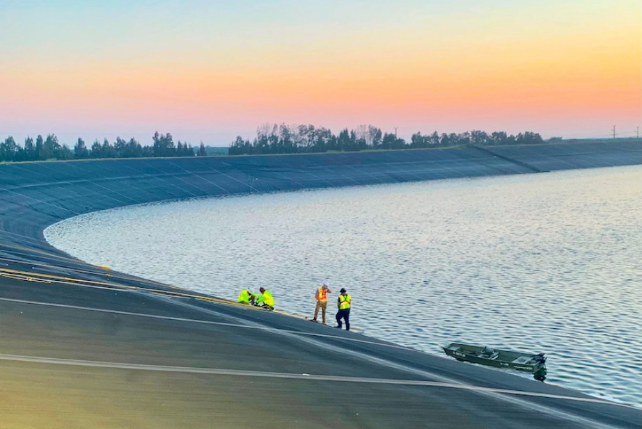 People standing on the edge of a large reservoir at sunset