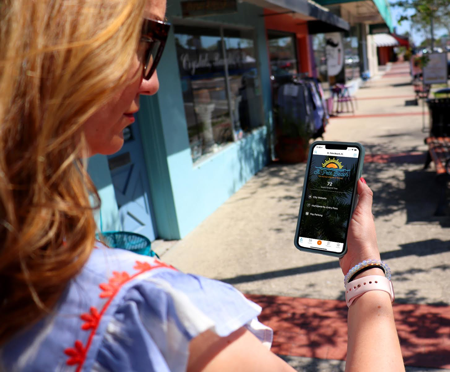 """A photo of a woman looking at a """"St. Pete Beach"""" app on her phone while walking  on a sidewalk"""