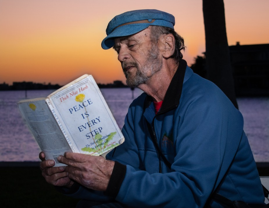 """A man in a boat captain hat reading a book titled """"Peace is Every Step"""" outside at sunset by the water."""