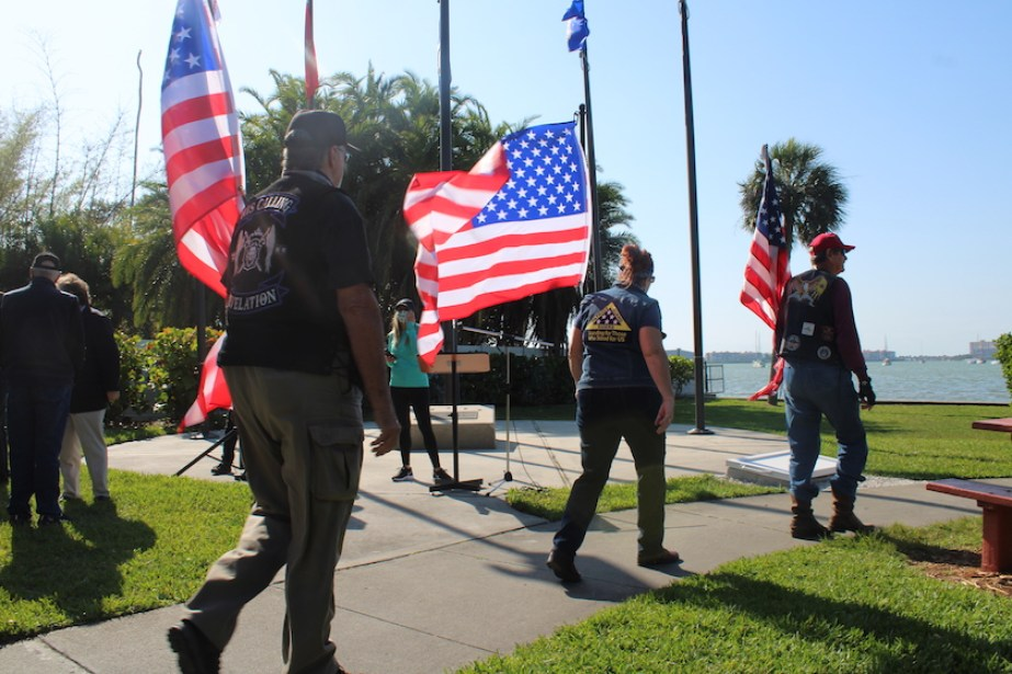A group of people walking and holding US flags.