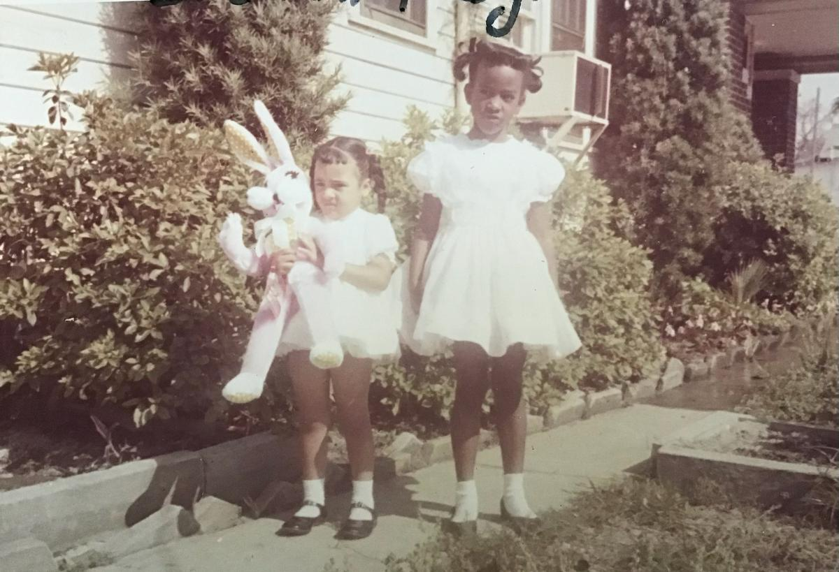 An old photo of two girls in dresses with an Easter rabbit outdoors.
