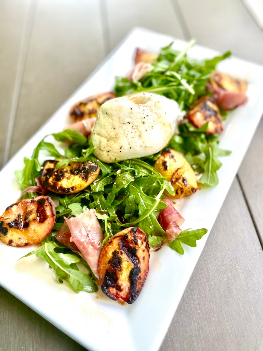 A salad of grilled peaches and cheese with arugula.