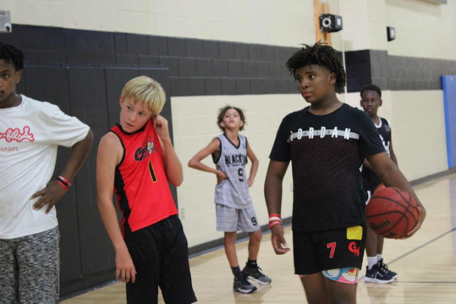 Boys in basketball clothes on an indoor court.