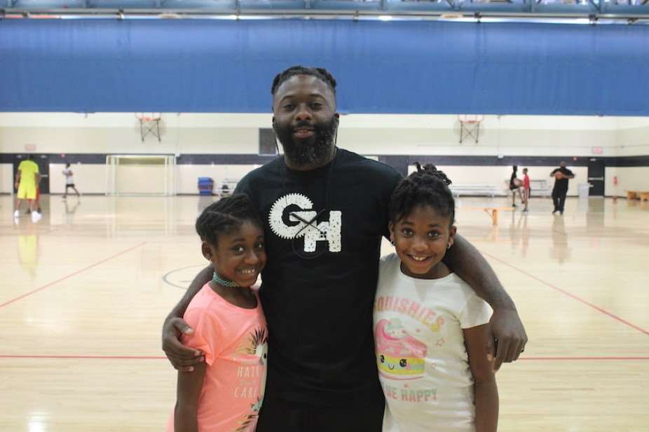 A man on a basketball court with his arms around to smiling girls.