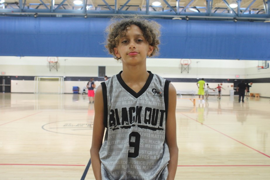 """A young boy on a basketball court with a basketball jersey that reads """"Black Out 9"""""""