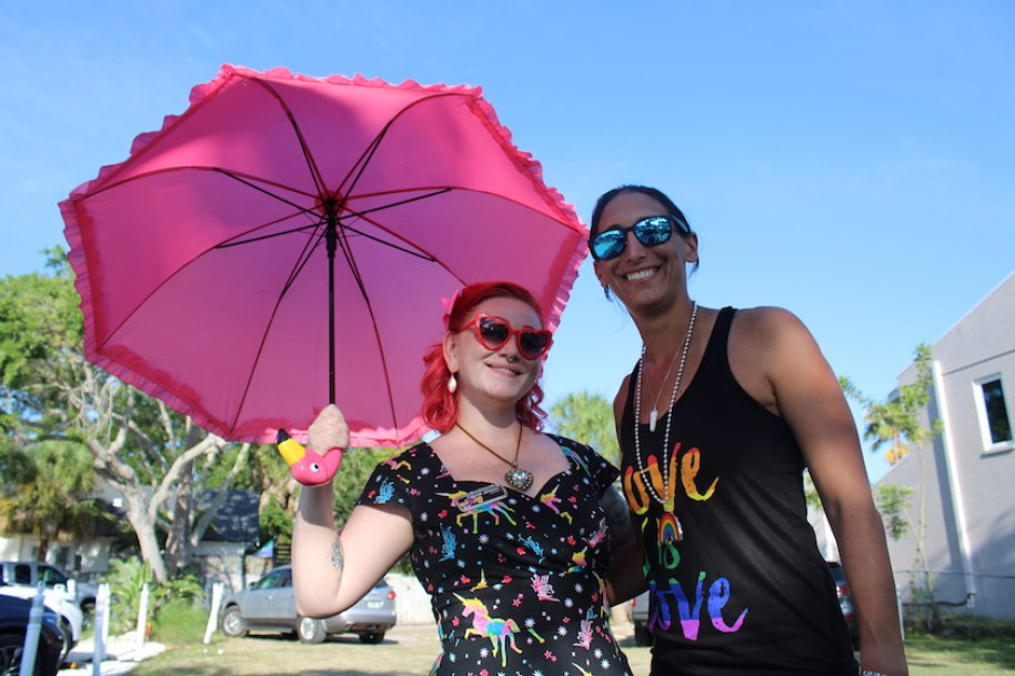 A woman with a pink umbrella and sunglasses posses with a taller woman in a black tank top and sunglasses outdoors.