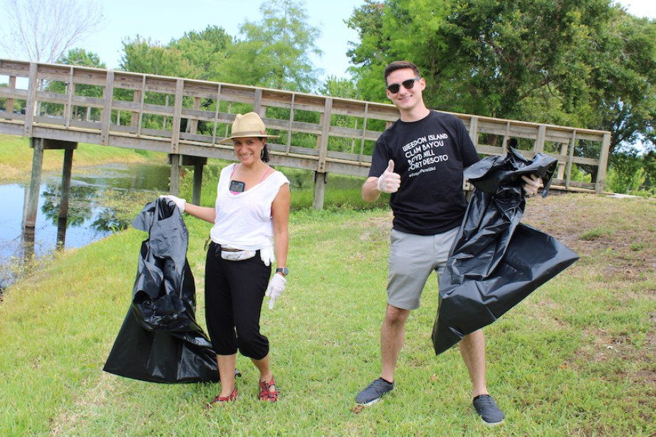 A man and a woman in a green park with black trash bags and a litter picker