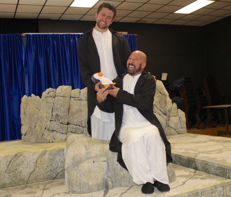 Two men dressed as penguins holding a stuffed penguin on a stage set.