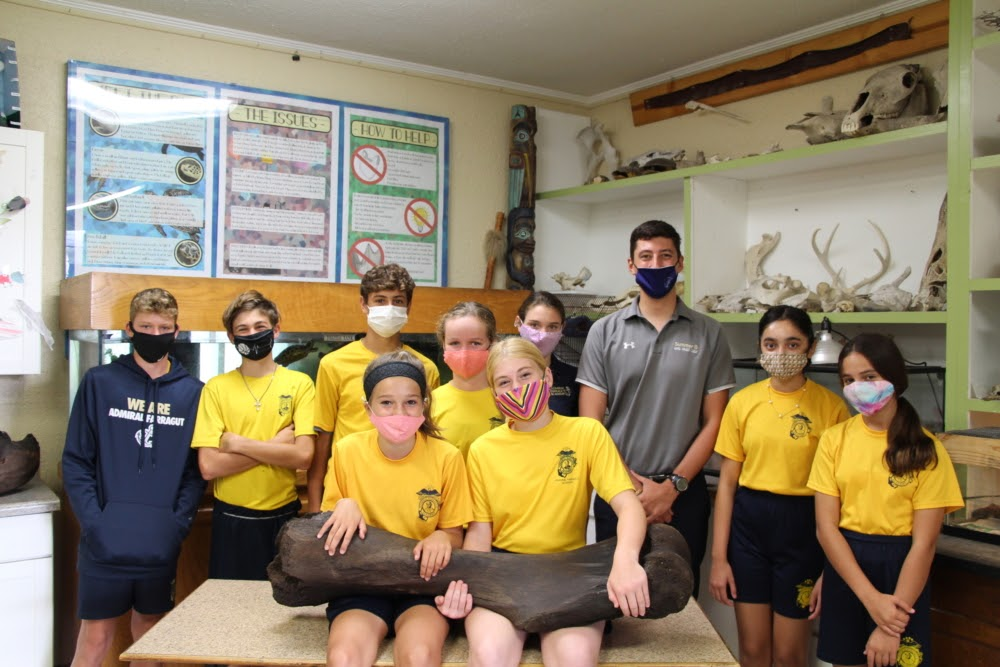 A classroom filled with students in yellow shirts and face masks, with two students holding a large black bone.