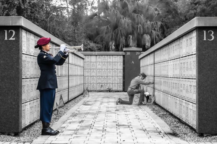 A person in military uniform playing a bugle at a military crypt near a man kneeling.