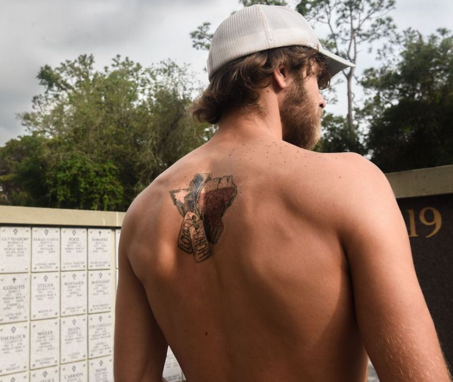 The back of a man with his shirt off showing a tattoo of Texas with military dog tags.