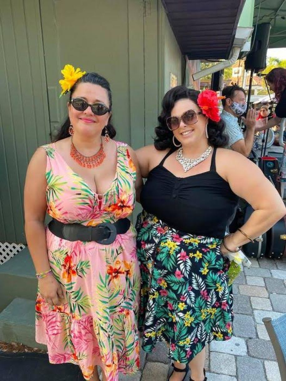 Two woman pose in pinup costumes and sunglasses.