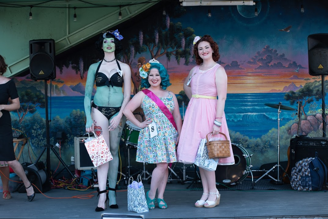 Three women pose on a stage in pinup costumes.
