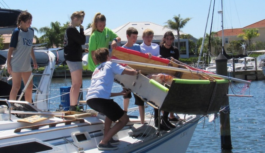 A group of teens trying to launch a homemade boat into the water.