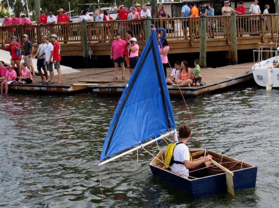 A teen sailing a homemade boat near a dock with a blue sail.