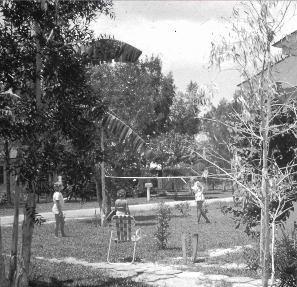 A black and white photo of people playing badminton with a net in a yard.