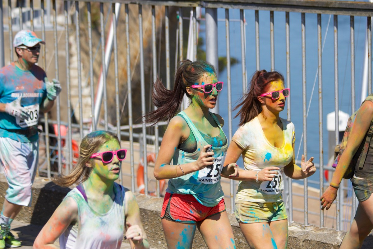People running with rainbow paint on them