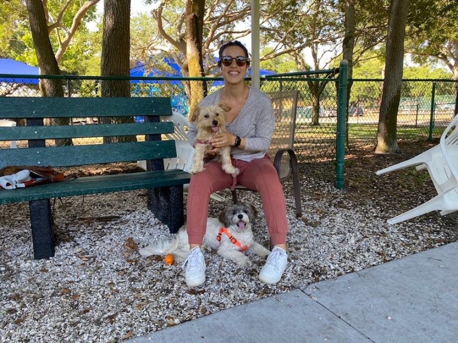 A woman on a green bench with a dog in her lap and at her feet.