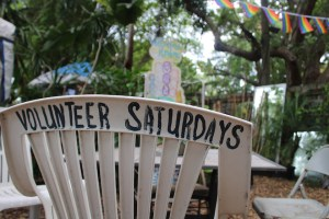 """A white plastic patio chair that reads """"Volunteer Saturdays"""""""