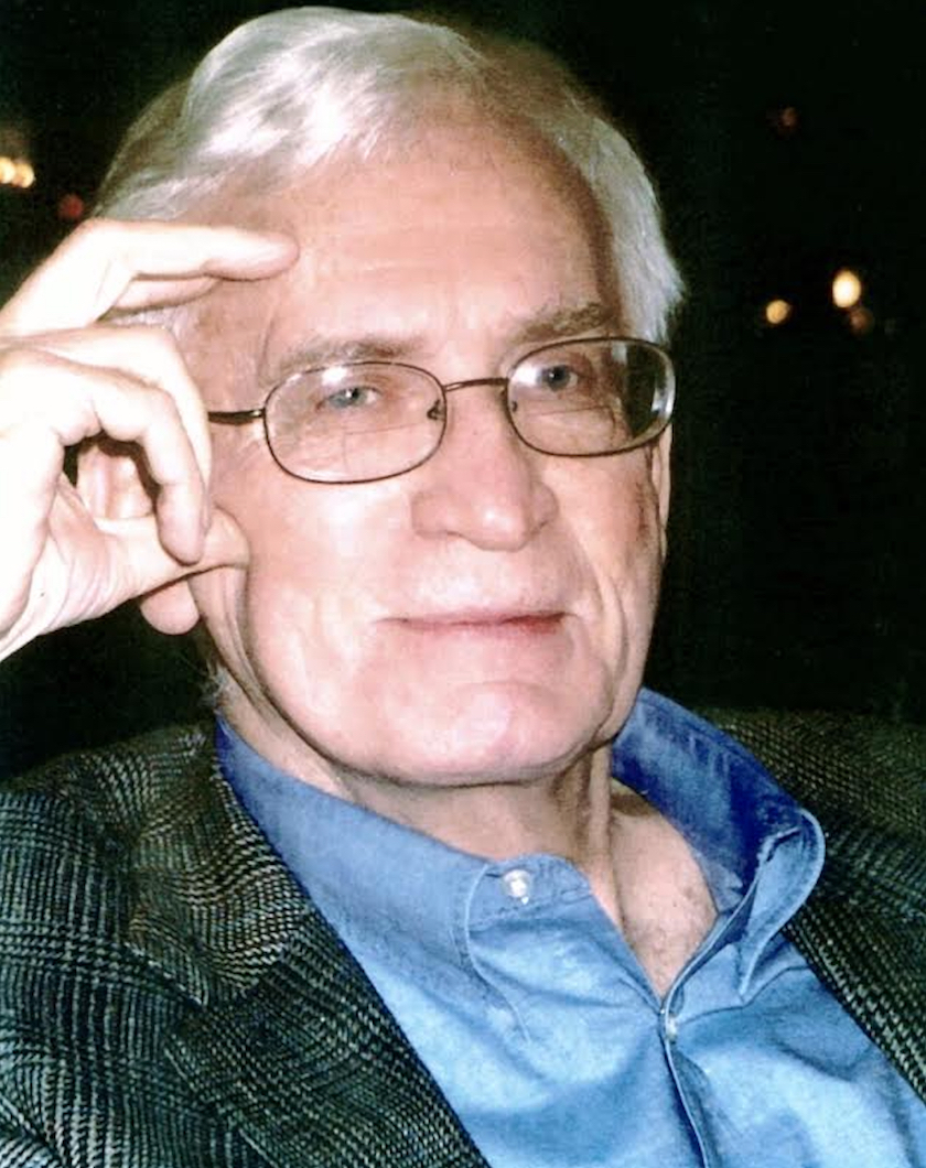 A head shot of a man with glasses and a blue shirt with his hand to his head.