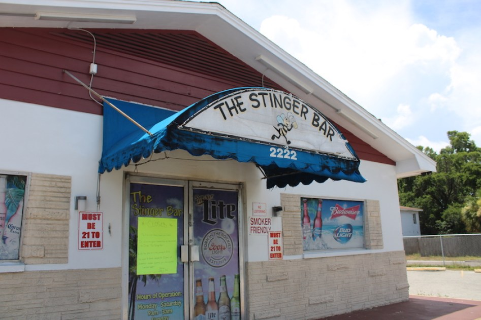 """A photo of the outside of a bar with an awning that reads """"The Stinger Bar"""""""