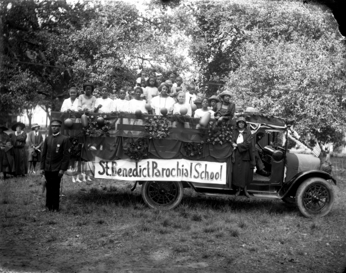 A black and white photo of children in a truck with a sign St. Benedict School around 1922.