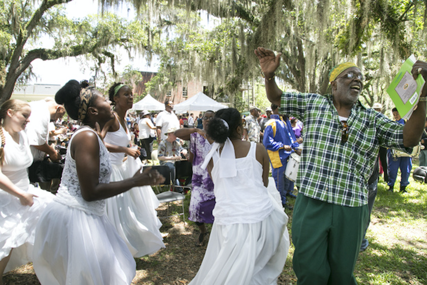 A photo of women in white dresses and a man in green plaid celebrating in a park.