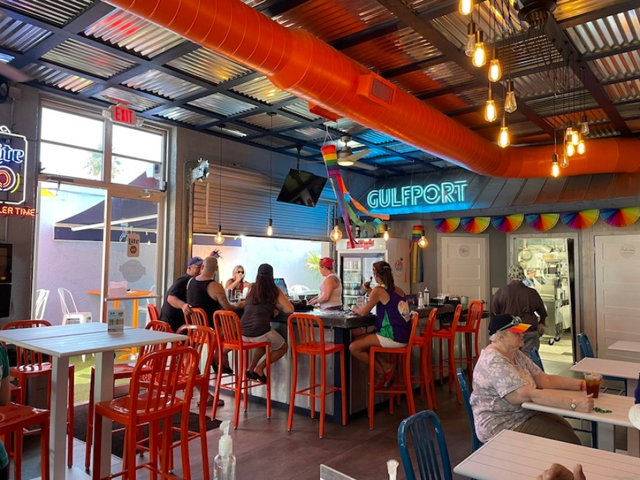 """A photo of the inside of a restaurant with a blue neon sigh reading """"Gulfport"""""""