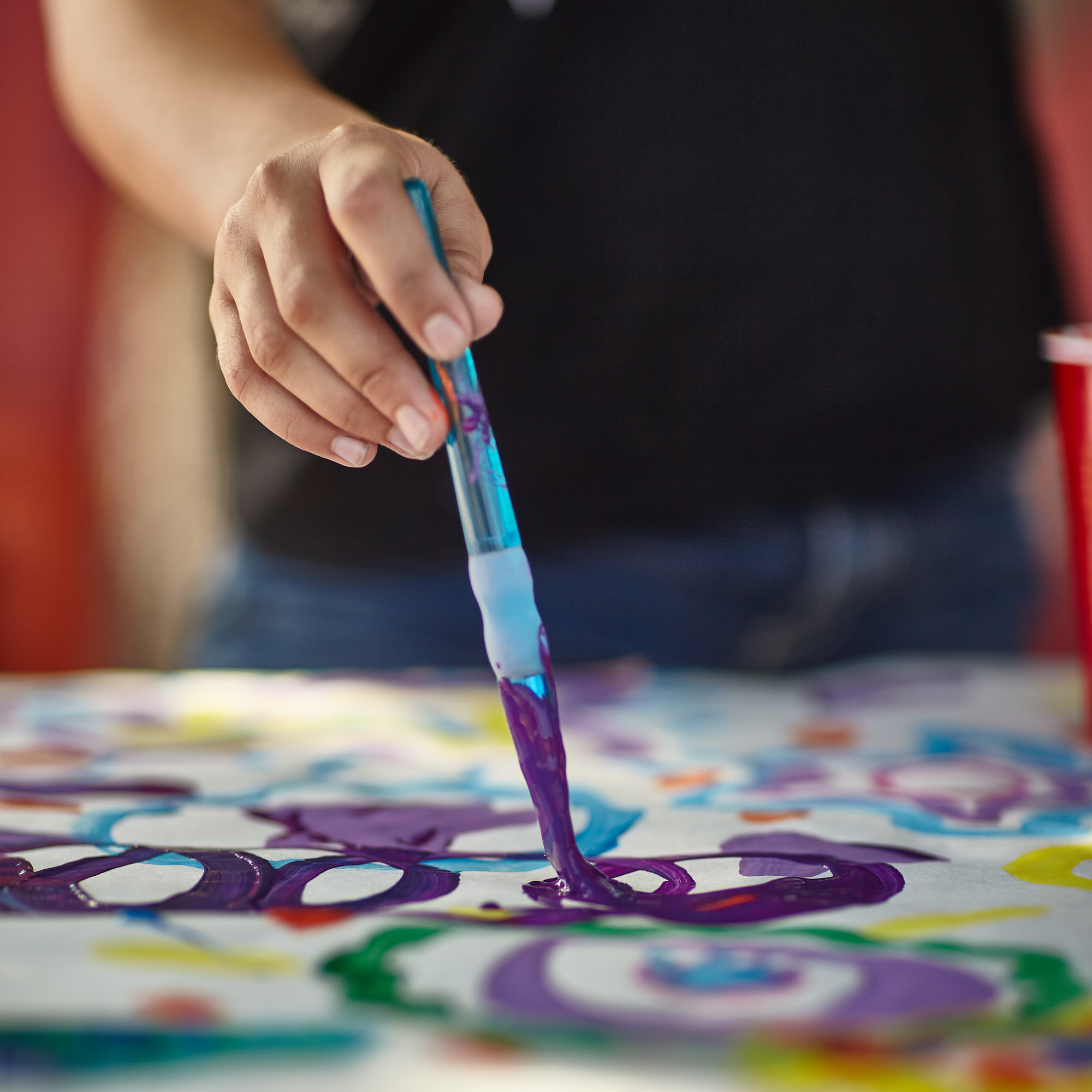 A close up of a hand with a paintbrush painting purple lines.