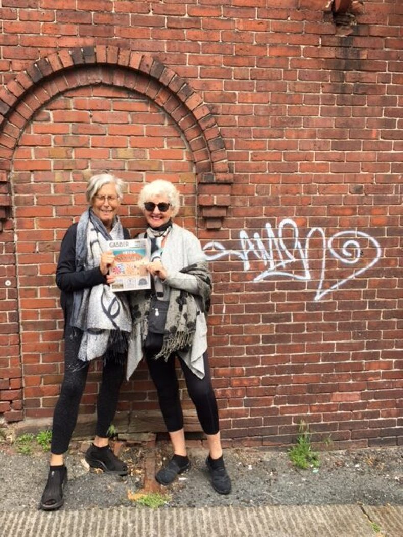 Two women use with a Gabber Newspaper in front of a red brick wall with graffiti on it.