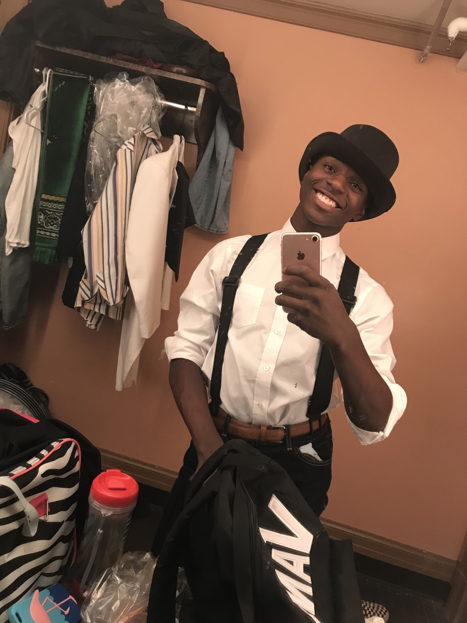 A young man in a white shirt with a black bowler hat and suspenders taking a selfie in a mirror.