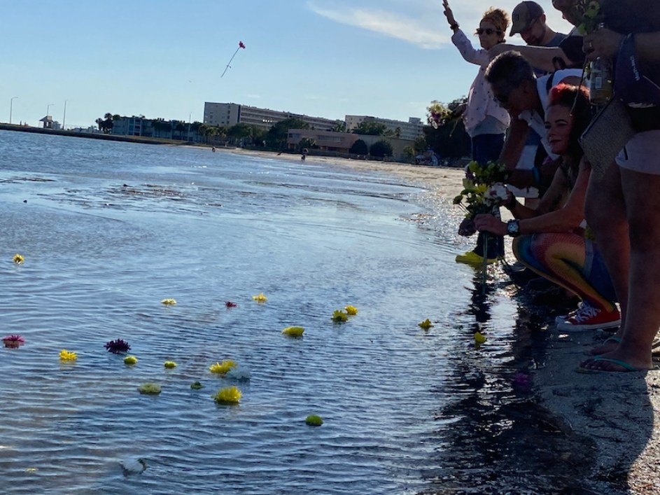 A group of people on a bech toss flowers into the water.