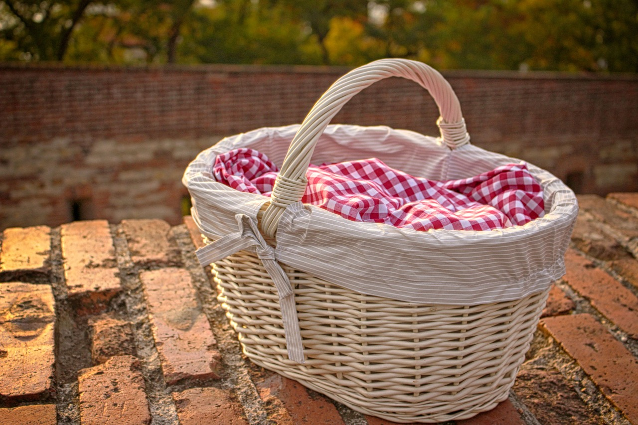 A photo of a white picnic basket with a gingham cloth on a brick patio.