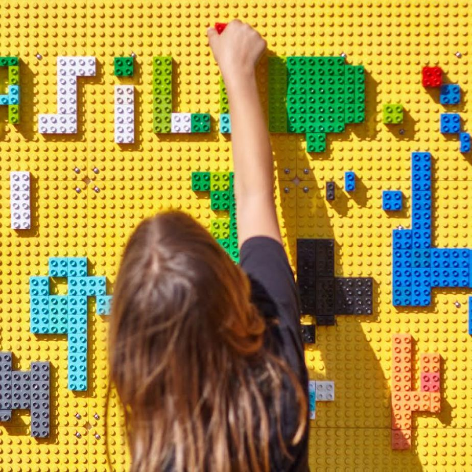A photo of a girl putting colorful toy blocks on a large yellow wall.