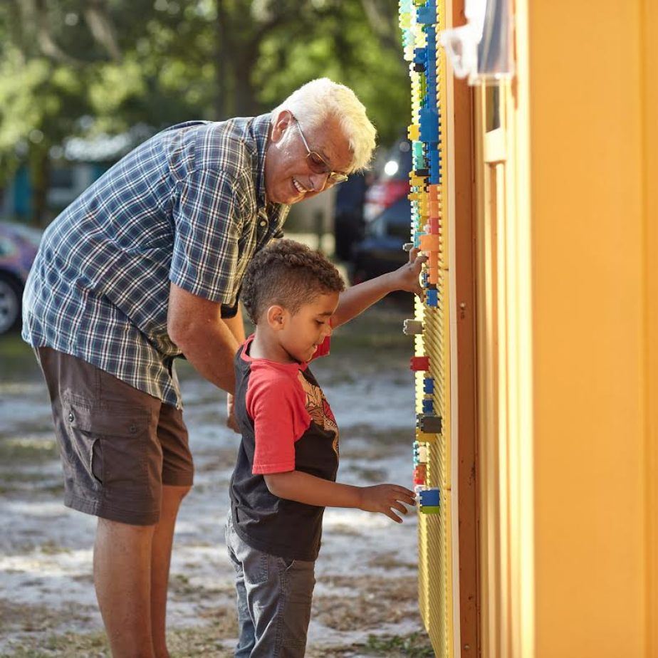 An older man with a young boy painting a wall.