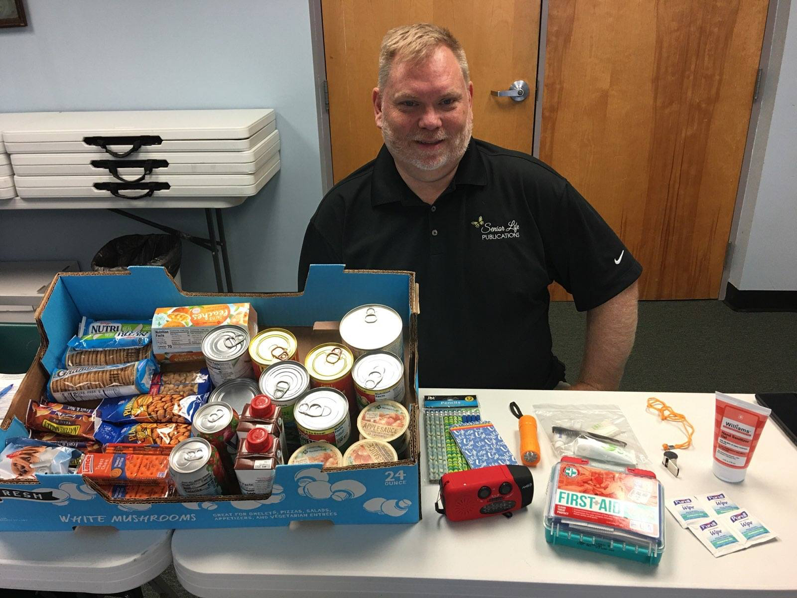 A man in an office with canned food and emergency supplies on his desk