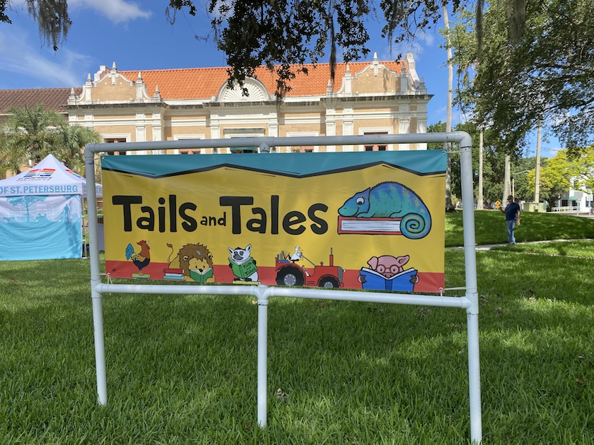 """A colorful sign outside that reads """"Tails and Tales"""""""