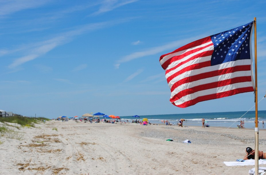 A daytime beach scene with a US flag in the foreground.