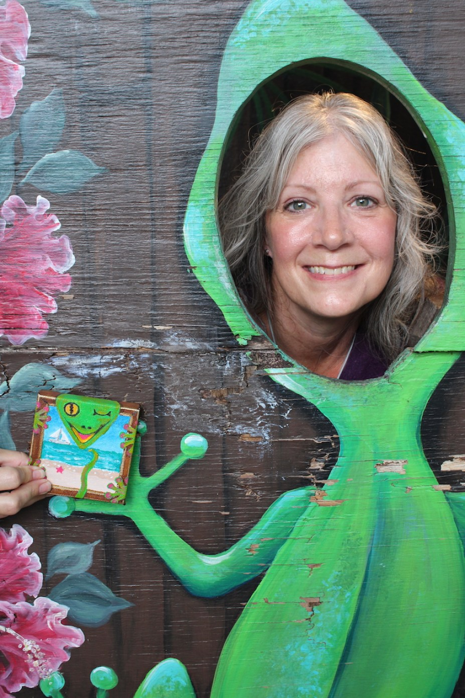 A woman with her head in a cutout of a green painted gecko on black background with a person holding a small square gecko art piece in the frame.