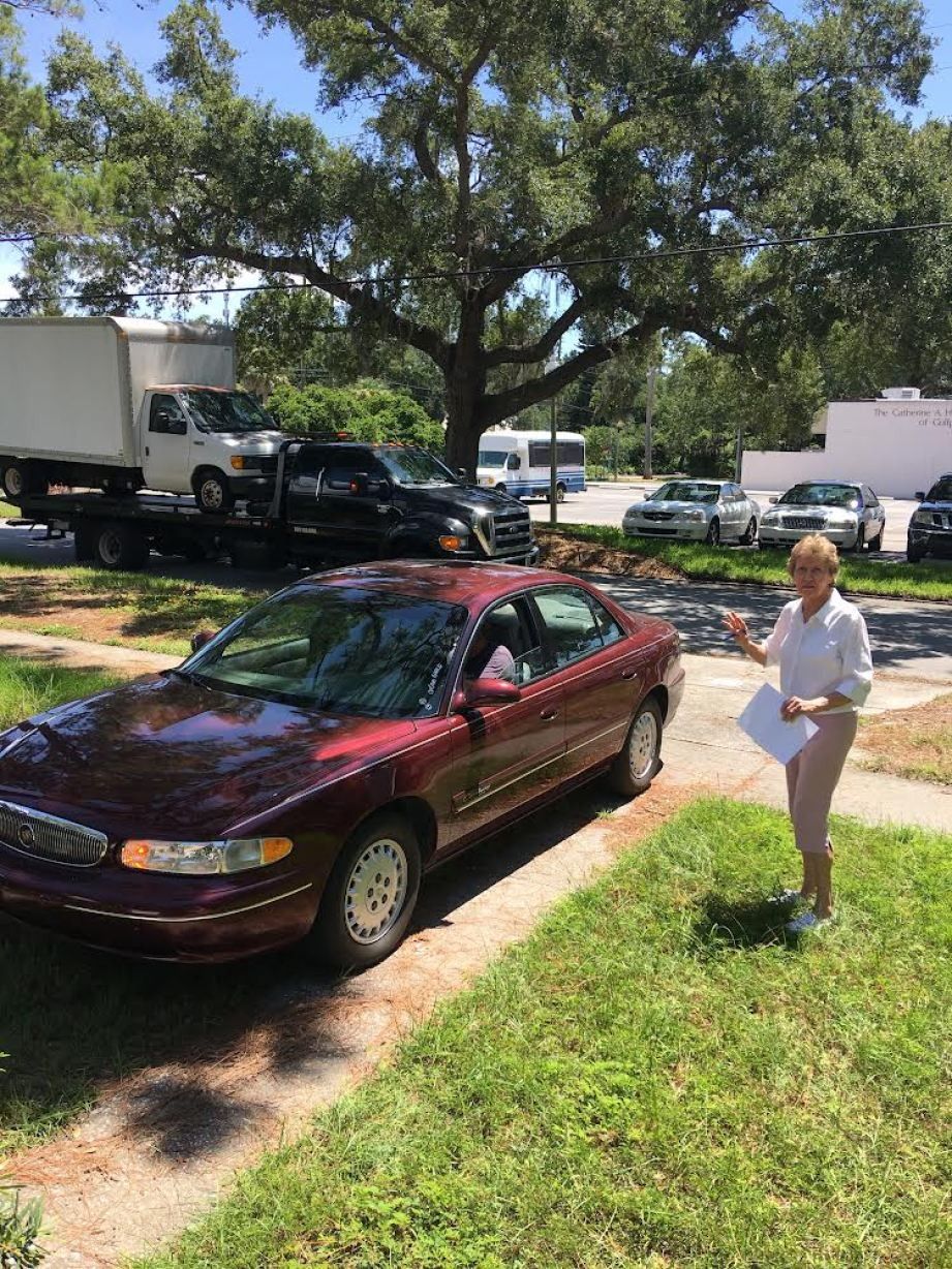 A woman holding a paper next to a maroon Buick sedan in a driveway, with a tow truck with another truck on in in the background.