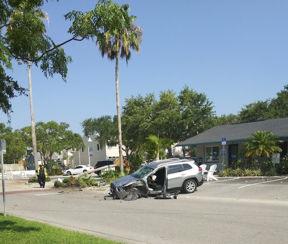 A photo taken from across a street of a silver SUV crashed in a parking lot in front of a building and palms trees.