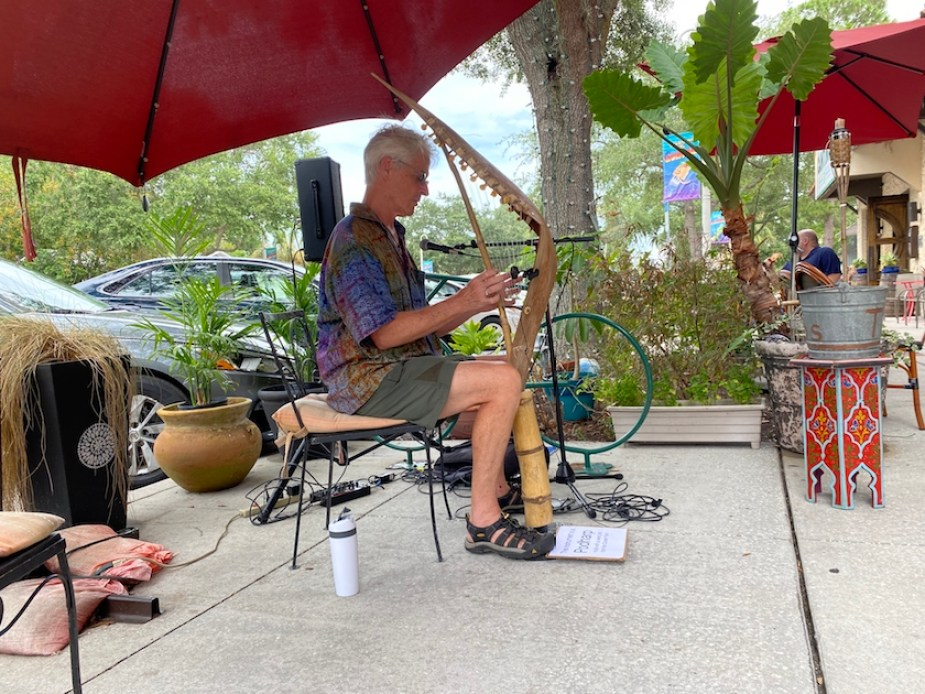 A photo of a man with a music sound system set up outside under a red umbrella, playing a musical instrument made from a palm tree pod.